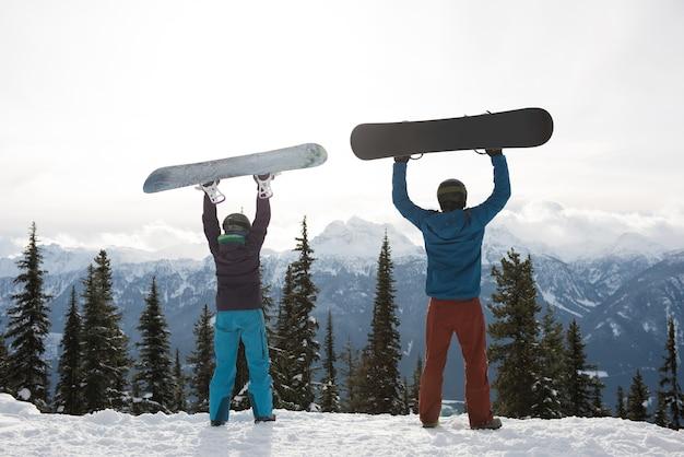 Vista trasera del hombre y la mujer sosteniendo snowboard en la montaña durante el invierno