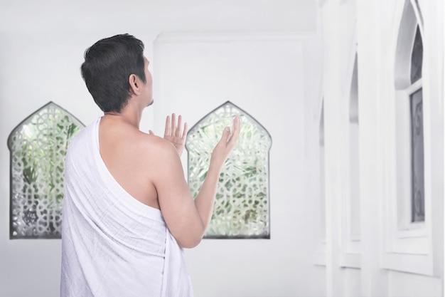 Vista trasera del hombre musulmán asiático reza a dios