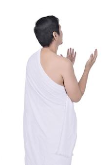 Vista trasera del hombre musulmán asiático en tela ihram rezando