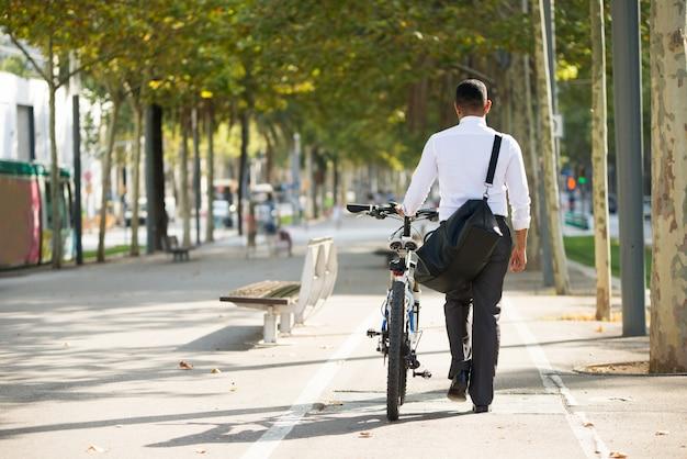 Vista trasera del hombre de negocios caminando con la bicicleta en el parque