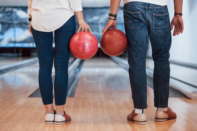 Vista trasera del hombre y la niña de pie con bolas de bol en las manos en el club