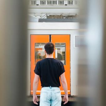 Vista trasera del hombre parado frente a la puerta del ferrocarril