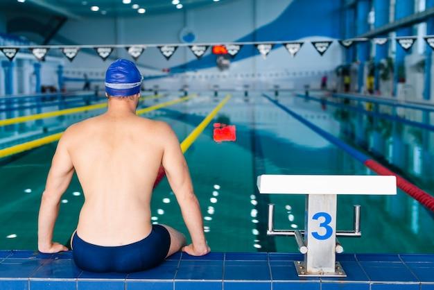 Vista trasera del hombre de pie en el borde de la piscina