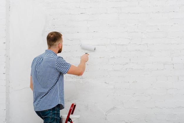 Vista trasera del hombre pintando la pared