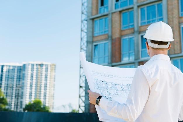 Vista trasera del hombre con planes de construcción