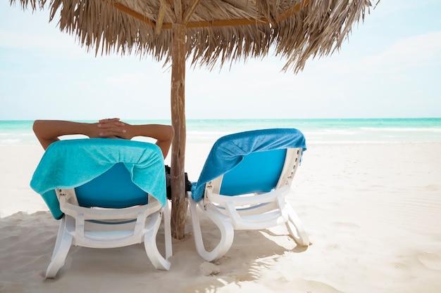 Vista trasera hombre relajante bajo el paraguas de palmeras en la playa del resort