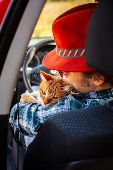 Vista trasera del hombre sentado en el asiento del conductor con un gato