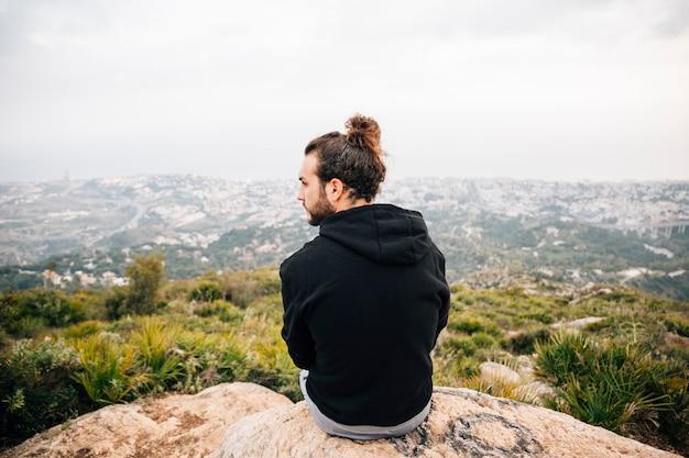 Vista trasera del hombre sentado en la cima de la roca con vistas a la vista a la montaña