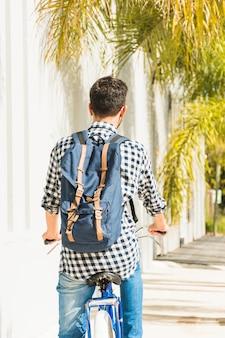 Vista trasera del hombre con su mochila azul montada en bicicleta.