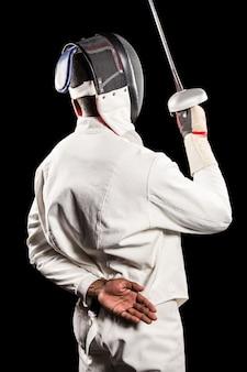 Vista trasera del hombre vestido con traje de esgrima practicando con espada