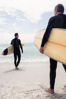 Vista trasera de hombres caminando por la playa con tabla de surf