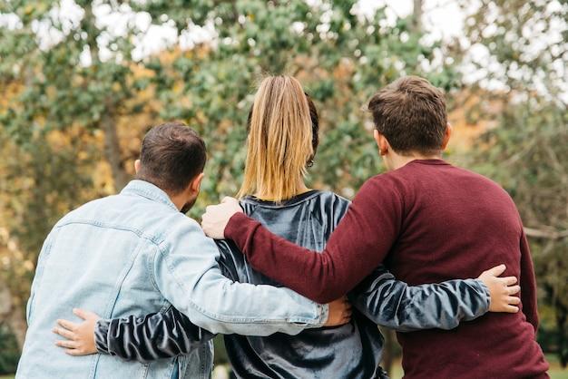 Vista trasera de hombres y mujeres abrazándose