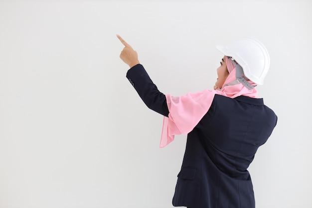Vista trasera inteligente ingeniería musulmana joven asiática vistiendo traje azul con confianza, apuntando y usando el teléfono móvil