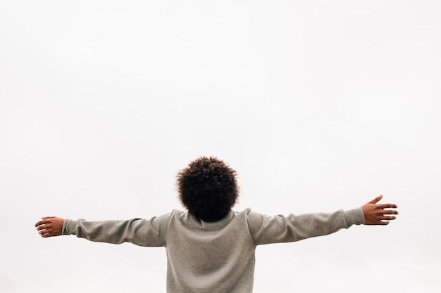 Vista trasera de un joven africano extendiendo su mano contra el fondo blanco.