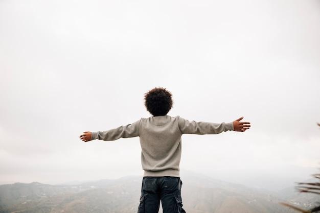 Vista trasera de un joven africano de pie en la cima de la montaña extendiendo su mano
