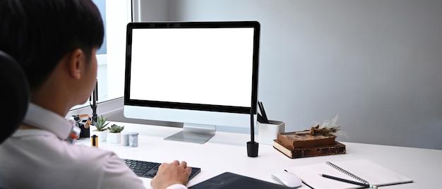Vista trasera del joven diseñador gráfico sentado en su espacio de trabajo frente a la computadora mientras trabaja en línea