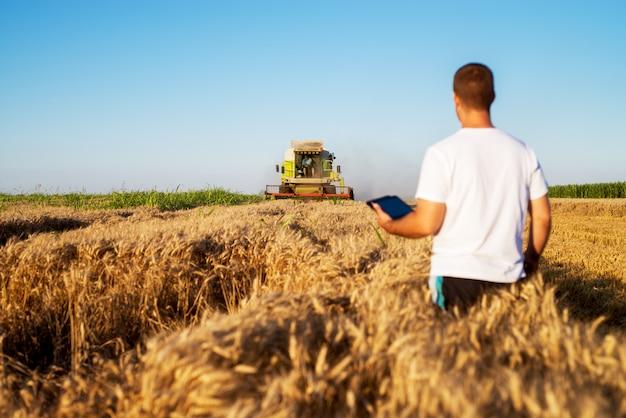 Vista trasera del joven ingeniero agrónomo de pie en un campo de trigo dorado con tableta y mirando a la cosechadora en el frente.