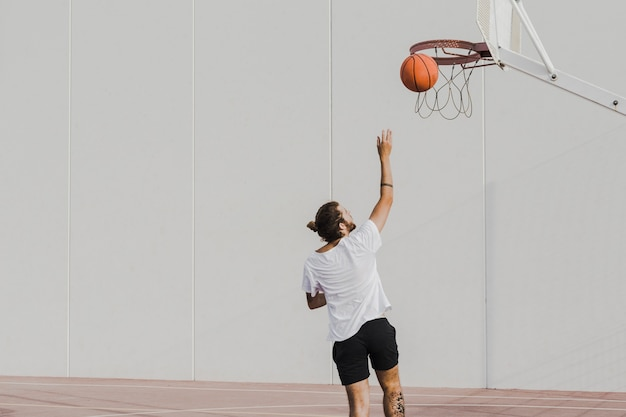 Vista trasera, de, un, joven, lanzamiento, baloncesto, en, aro