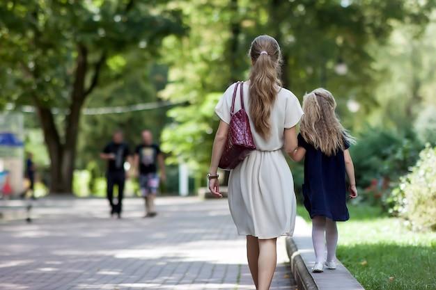 Vista trasera de la joven madre caminando con niña