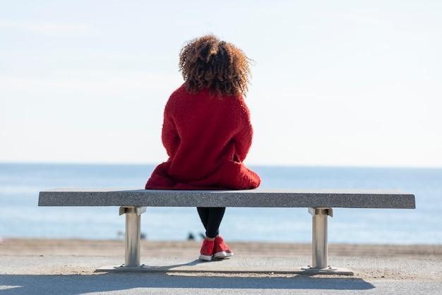 Vista trasera de una joven mujer rizada con chaqueta de mezclilla roja sentada en un banco mientras mira hacia el horizonte sobre el mar