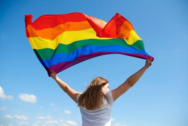 Vista trasera del joven ondeando la bandera del arco iris