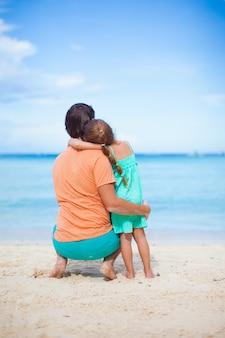Vista trasera del joven padre y su adorable hijita se divierten en la playa