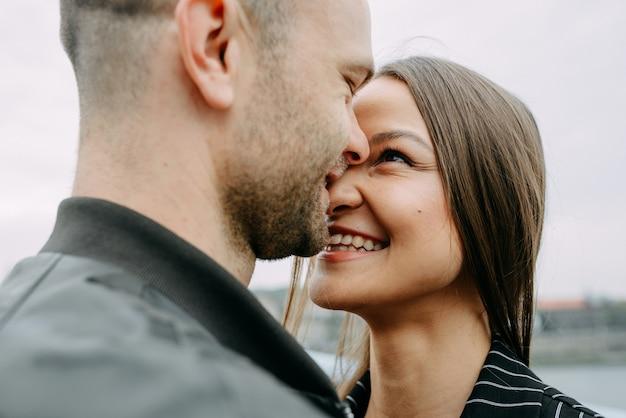 Vista trasera de una joven pareja sentada al lado de un lago tocando sus cabezas en el amor.
