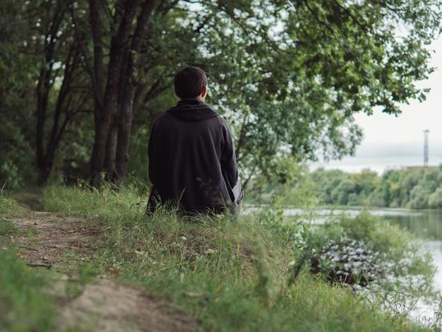 Vista trasera del joven. siéntese en la orilla del río en tiempo nublado. soledad