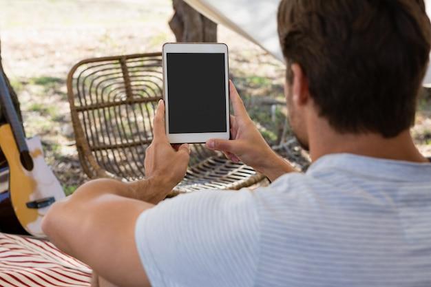 Vista trasera del joven usando tableta en tienda