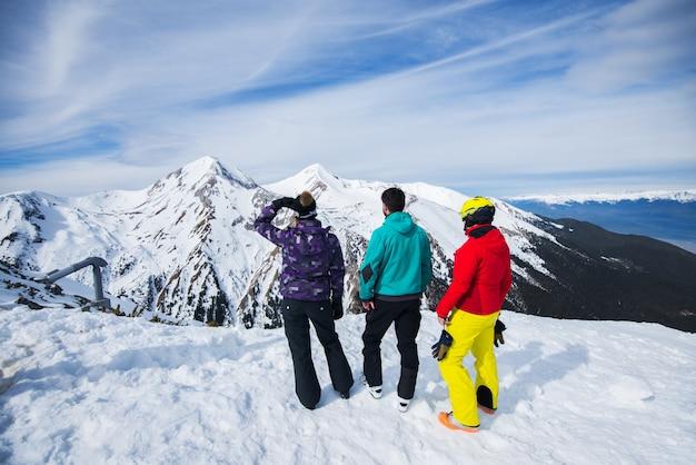 Vista trasera de jóvenes disfrutando en invierno cubierto de nieve en la cima de la montaña