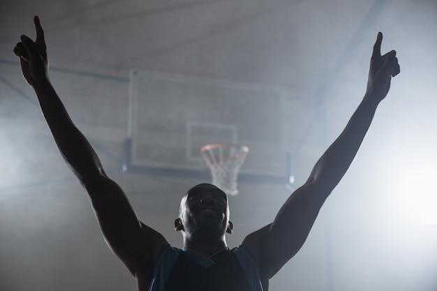 Vista trasera de un jugador de baloncesto con los brazos en el aire.