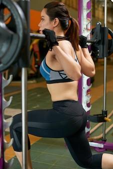Vista trasera lateral de mujer en forma entrenando con peso pesado en la máquina smith