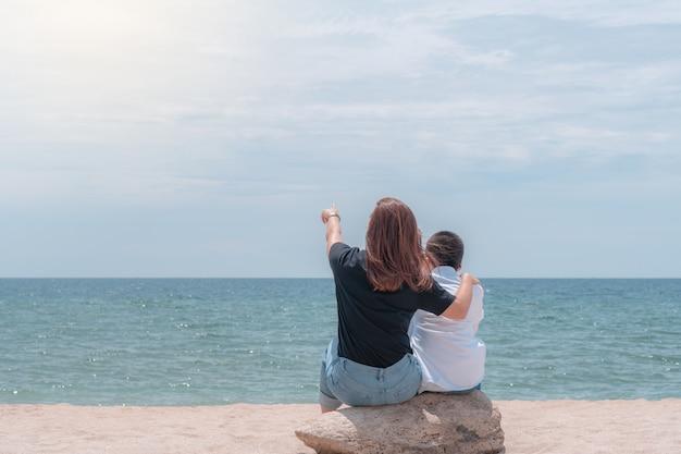 Vista trasera de la madre abraza a un hijo por los hombros sentado en la playa y mirando al mar