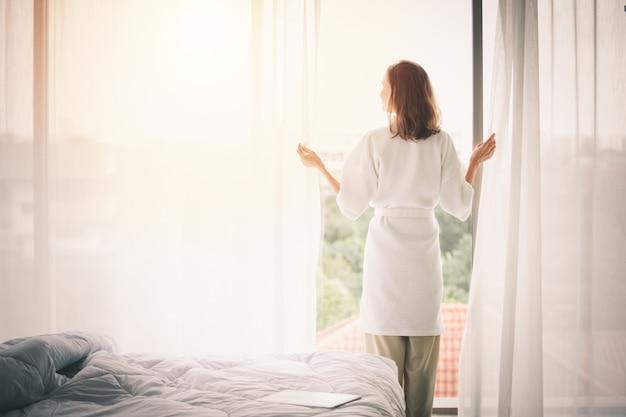 Vista trasera de la mujer abriendo cortinas en un dormitorio blanco.