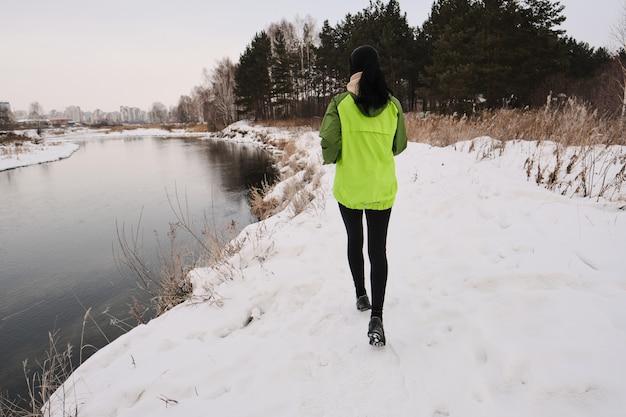 Vista trasera de la mujer en chaqueta verde que corre a lo largo de la orilla del invierno con pasto seco largo