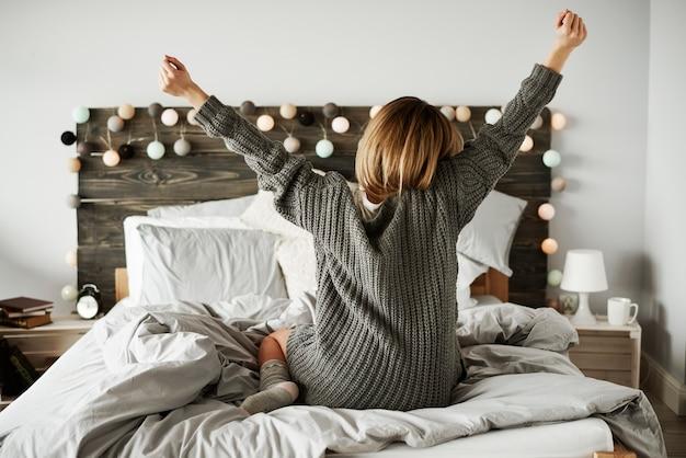 Vista trasera, de, mujer, extensión, en, ella, cama