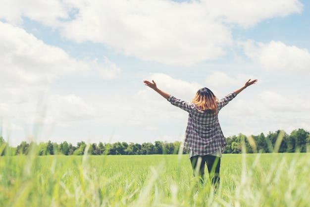 Vista trasera de mujer joven con los brazos abiertos en el prado