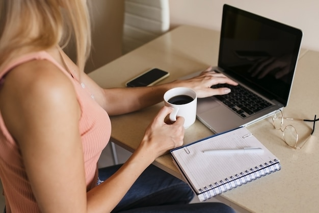 Vista trasera de una mujer joven que trabaja en una computadora portátil en casa