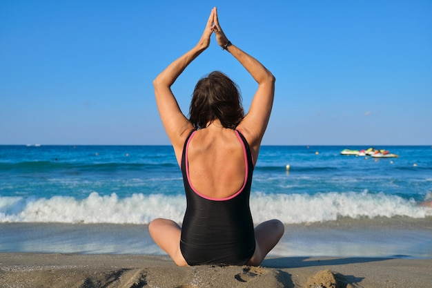 Vista trasera de una mujer de mediana edad en traje de baño sentada en la orilla en posición de loto