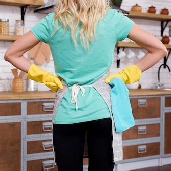 Vista trasera de una mujer de pie en la cocina con las manos en la cintura con guantes de goma