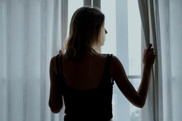 Vista trasera de una mujer de pie junto a la ventana