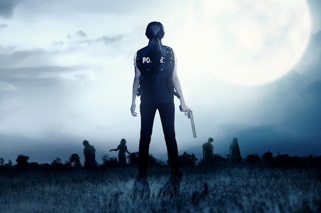 Vista trasera de la mujer policía asiática con la pistola en la mano frente a los zombies en el campo de hierba