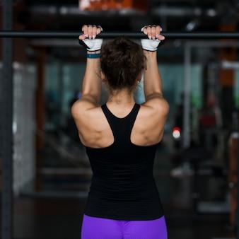 Vista trasera mujer realizando pull-ups