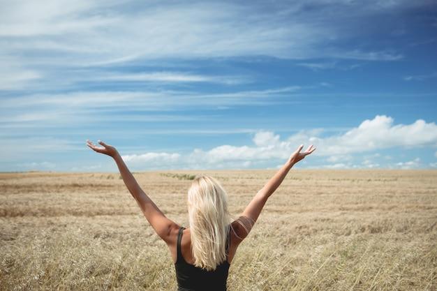 Vista trasera de la mujer rubia de pie en el campo