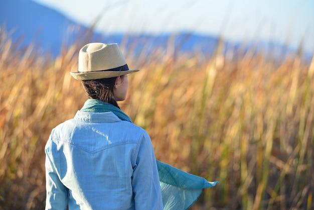 Vista trasera de mujer con sombrero contemplando la naturaleza