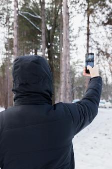 Vista trasera, de, un, mujer, toma, fotografía, en, teléfono móvil