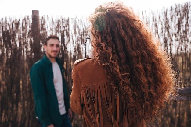 Vista trasera mujer tomando fotos del hombre.
