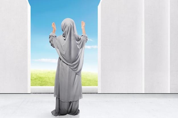 Vista trasera de la niña asiática en velo de pie levantar la mano y rezar en la mezquita