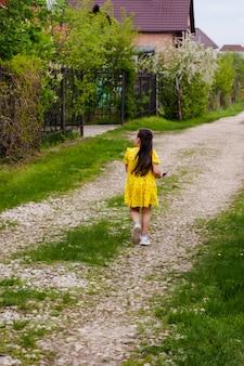 Vista trasera de una niña caminando por un sendero en el pueblo entre las casas del pueblo