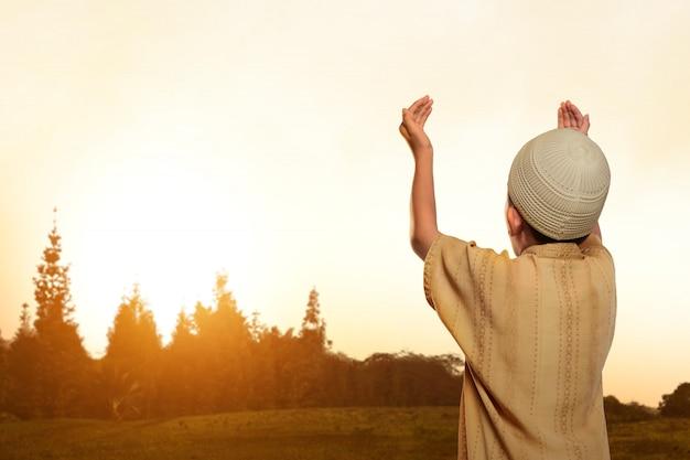 Vista trasera del niño musulmán asiático con gorra rezando a dios
